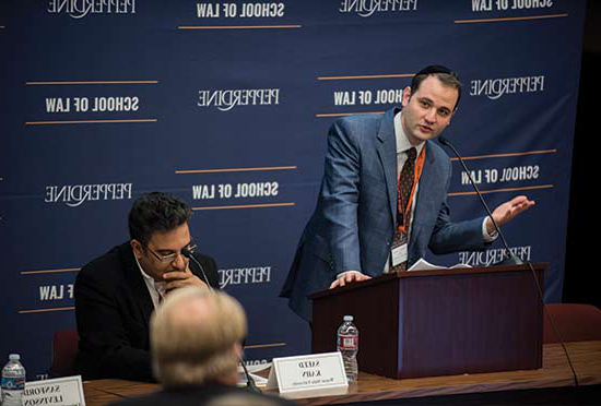 Professor Michael Helfand speaking at a podium in front of a blue School of Law Sign at a Nootbaar event