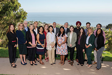 The Straus Institute staff standing for a group photo in front of the ocean at the School of Law