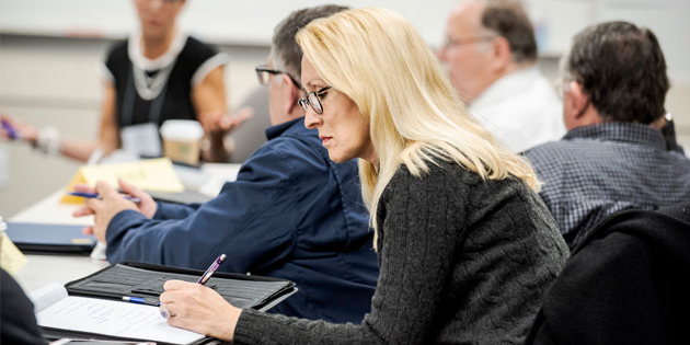woman taking notes in professional program