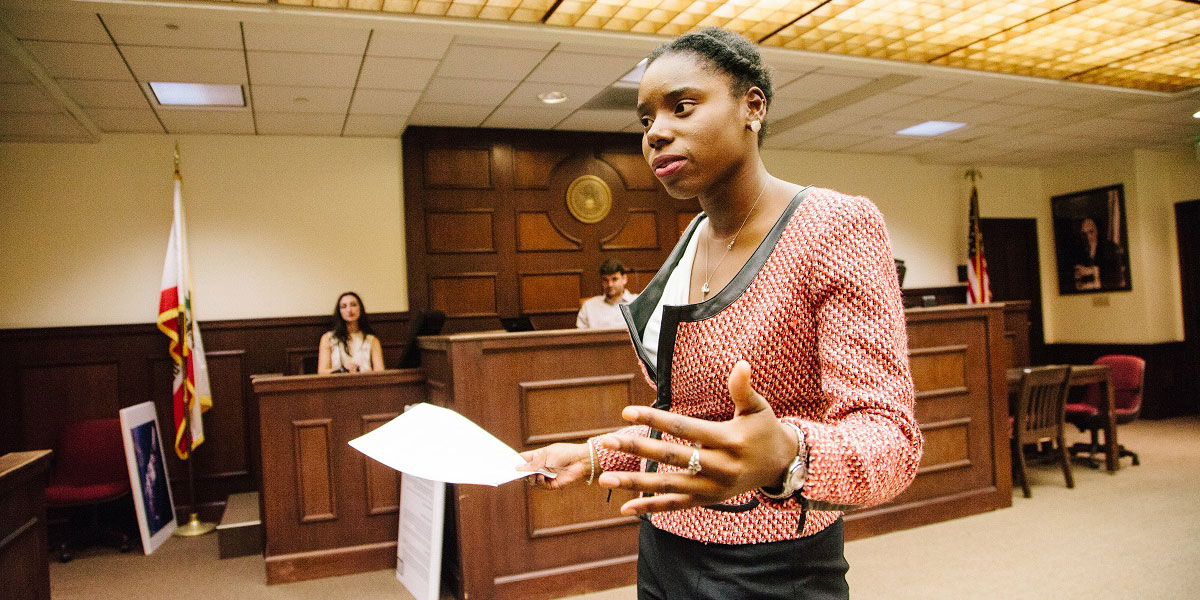 Student speaking and holding a paper in the trial courrtroom